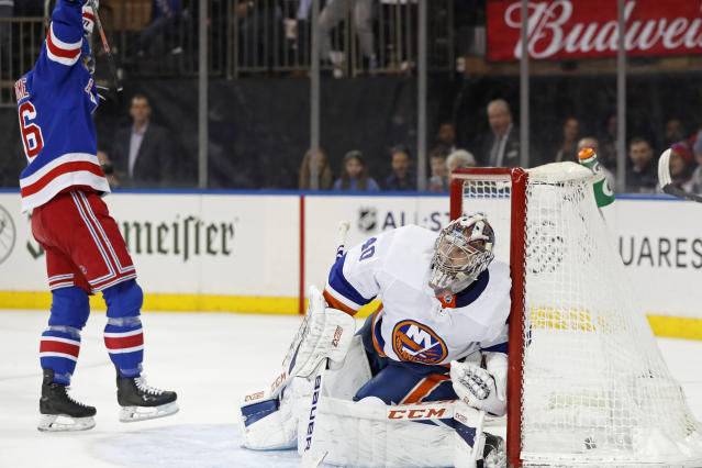 New York Rangers center Ryan Strome, left, celebrates as New York Islanders goaltender Semyon Varlamov (40) reacts after allowing a goal to Rangers defenseman Adam Fox during the second period of an NHL hockey game, Monday, Jan. 13, 2020, in New York. (AP Photo/Kathy Willens)