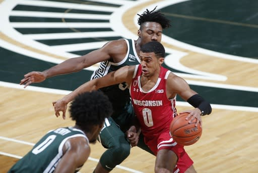 Wisconsin's D'Mitrik Trice, right, drives against Michigan State's Julius Marble II during the first half of an NCAA college basketball game, Friday, Dec. 25, 2020, in East Lansing, Mich. (AP Photo/Al Goldis)