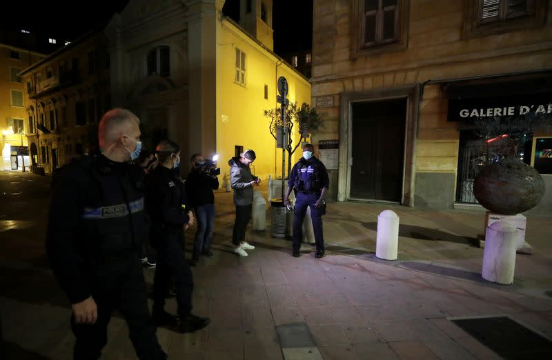 FILE PHOTO: Police officers check a person in Nice as the French Riviera city prepares for a new nightly curfew imposed in an effort to combat the the coronavirus