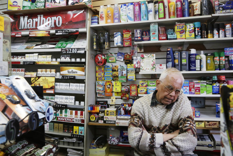 Harry Patel, an employee of Blondie's Deli and Grocery, talks on the phone while waiting for customers in New York, Monday, March 18, 2013. A new anti-smoking proposal would make New York the first city in the nation to keep tobacco products out of sight in retail stores. Mayor Michael Bloomberg says the goal is to reduce the youth smoking rate. The legislation would require stores to keep tobacco products in cabinets, drawers, under the counter, behind a curtain or in another concealed spot. They could only be visible when an adult is making a purchase or during restocking. (AP Photo/Mark Lennihan)
