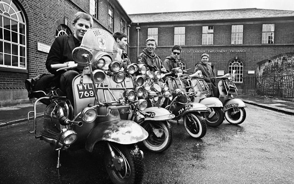 The mods and rockers were two conflicting British youth subcultures of the early to mid-1960s. Media coverage of mods and rockers fighting in 1964 sparked a moral panic about British youths, and the two groups became labelled as folk devils. John Rogers on his scooter with friends in peckham, 6th May 1964. (Photo by Cyril Maitland/Mirrorpix/Getty Images)  - Getty