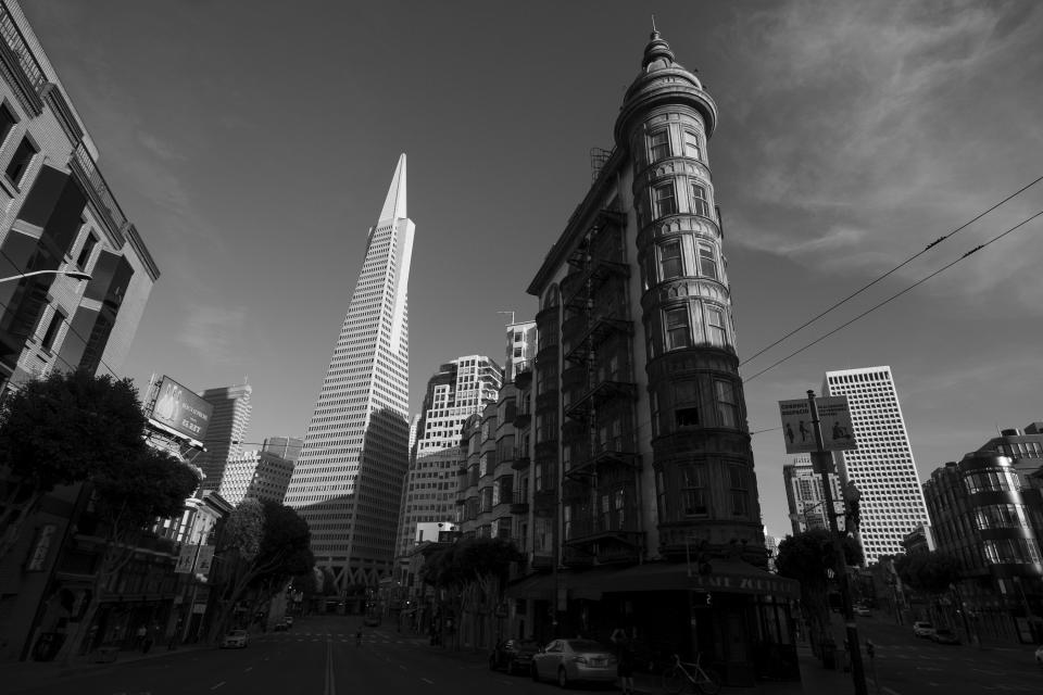 Late light falls on Francis Ford Coppola's Sentinel Building, right, and the Transamerica Pyramid in San Francisco on May 7, 2020. Normally, the months leading into summer bring bustling crowds to the city's famous landmarks, but this year, because of the coronavirus threat they sit empty and quiet. Some parts are like eerie ghost towns or stark scenes from a science fiction movie. (AP Photo/Eric Risberg)
