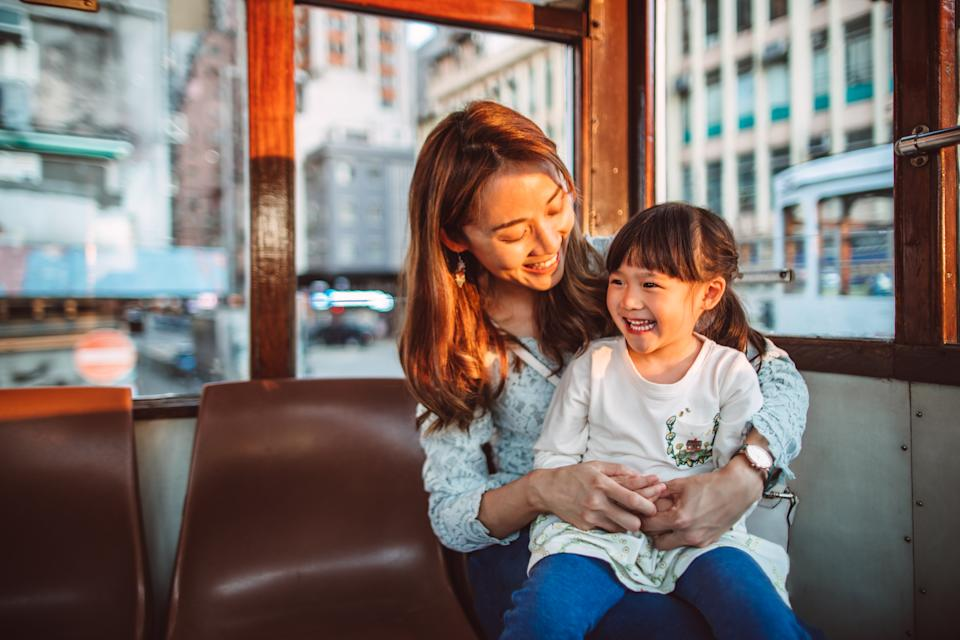 Young Asian mother playing joyfully with her lovely little daughter while riding on city tram in early evening.