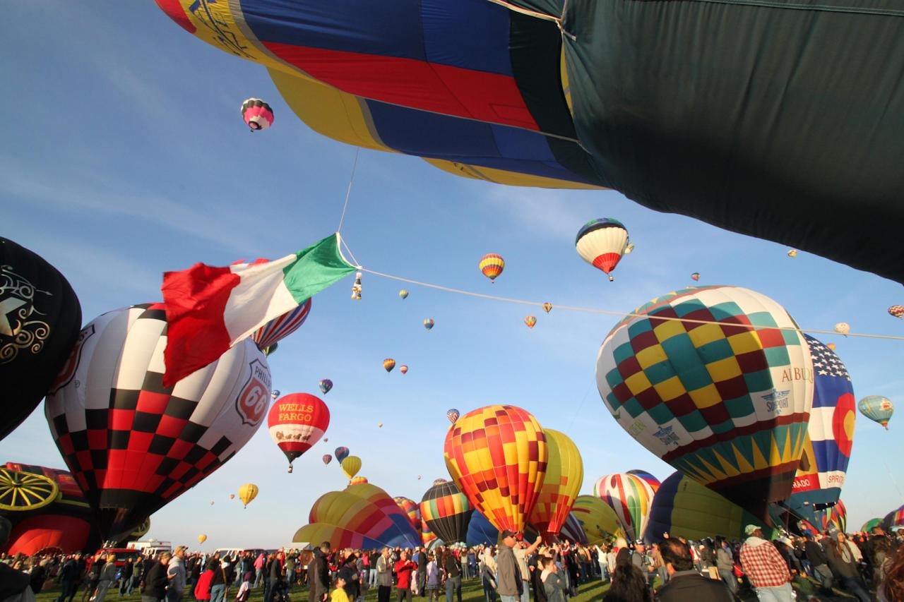 Thousands of spectators mingle among inflating hot air balloons at the 40th Albuquerque International Balloon Fiesta in Albuquerque, N.M., on Sunday, Oct. 2, 2011. Fiesta organizers said 550 balloons and 600 pilots from around the world are registered for this year's annual event. (AP Photo/Susan Montoya Bryan)