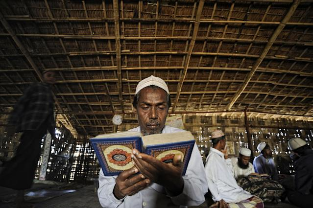 In this Nov. 30 2013 photo, Mohamad Iris, father of Senwara and Mohamad, prays at a makeshift mosque at the Ohn Taw refugee camp on the outskirts of Sittwe, Myanmar. After his tiny Muslim village in Myanmar's northwest Rakhine had been destroyed in a fire set by an angry Buddhist mob, the two children, 9- and 15-years old, became separated from the family. (AP Photo/Kaung Htet)
