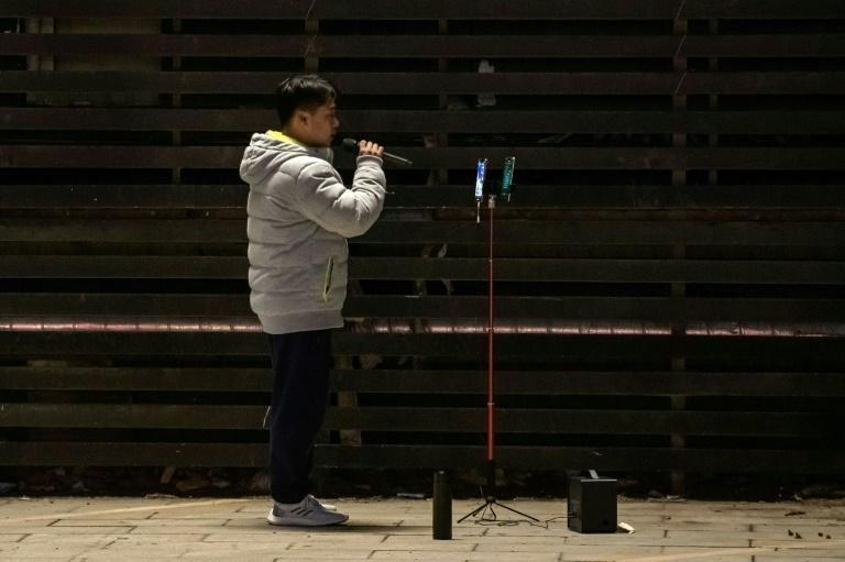 Chinese former champion gymnast Zhang Shangwu sings and performs in a parking lot for money