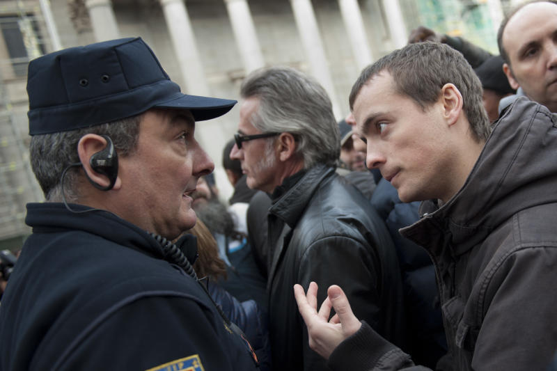 A demonstrator argues with a police officer during a protest outside the Parliament as the Spanish Parliament considers whether to admit a popular petition to change mortgage laws and halt evictions of those unable to pay mortgages to a vote in Madrid, Tuesday, Feb. 12, 2013. The government agreed to consider changes to the law on mortgages after pressure from opposition parties and a growing public outcry, including a petition that was signed by 1.4 million people – enough signatures to force Parliament to discuss alterations to the law in a special session. (AP Photo/Daniel Ochoa de Olza)