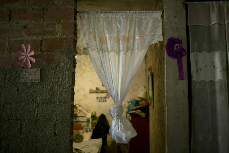 In this Tuesday, Feb. 19, 2019 photo, a curtain hangs in the doorway of what was the bedroom of Jhonny Godoy in La Vega slum of Caracas, Venezuela. According to his family, two days after proclaiming his opposition to President Nicolas Maduro on Twitter, rifle-wielding special police agents wearing black masks stormed into their home, pulled him outside and shot the 29-year-old to death. (AP Photo/Ariana Cubillos)