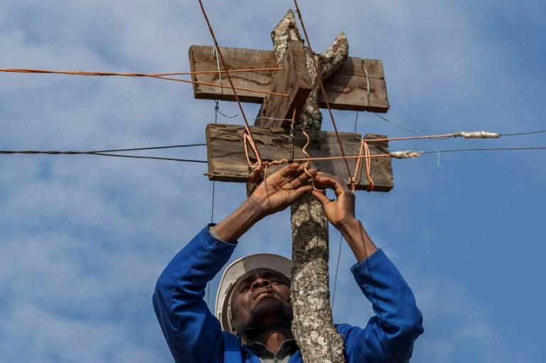 Metal cables strung along the top of tree stumps take the power from the tiny hydro plant to the village (AFP/AMOS GUMULIRA)