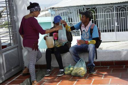 Marlon Carrillo (R) sells fruits bought in Venezuela to a customer in Cucuta, Colombia December 15, 2017. REUTERS/Carlos Eduardo Ramirez