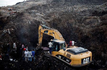Rescue workers watch as excavators dig into a pile of garbage in search of missing people following a landslide when a mound of trash collapsed on an informal settlement at the Koshe garbage dump in Ethiopia's capital Addis Ababa