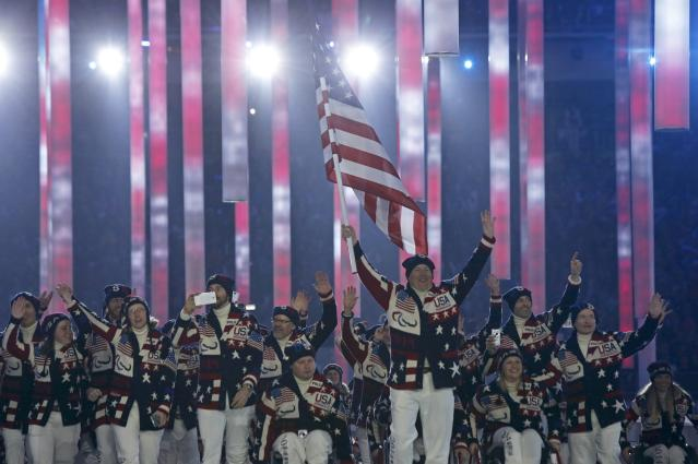REFILE - CORRECTING TEAM U.S. Team flag-bearer Jon Lujan (C), leads his country's contingent during the opening ceremony of the 2014 Paralympic Winter Games in Sochi, March 7, 2014. REUTERS/Alexander Demianchuk (RUSSIA - Tags: SPORT OLYMPICS)