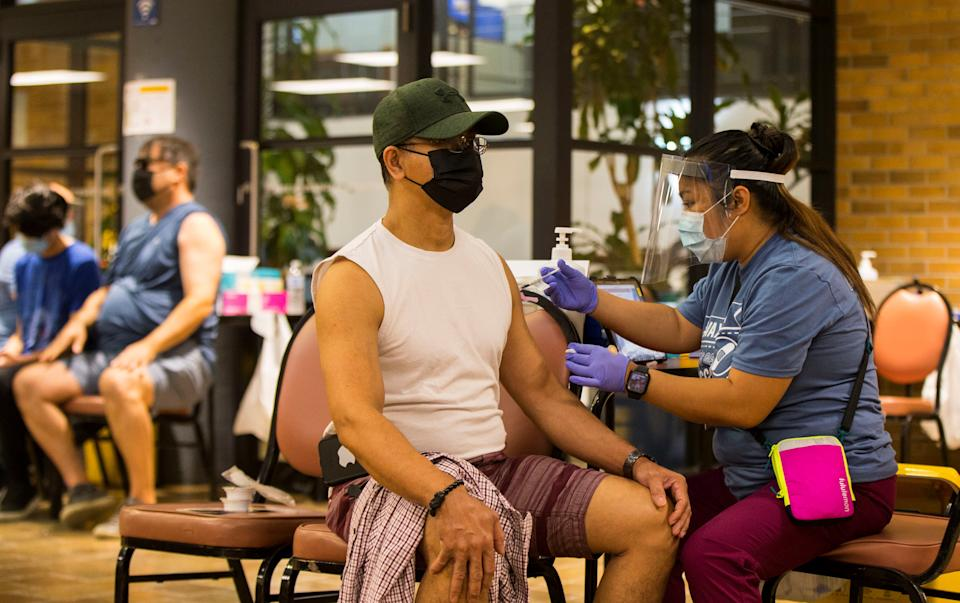 A man wearing a face mask receives a dose of the COVID-19 vaccine at a vaccination clinic in Mel Lastman Square in Toronto, Canada, on July 24, 2021. The City of Toronto kicked off a weekend-long vaccination clinic here on Saturday, welcoming walk-ins to anyone aged 12 and older for the COVID-19 vaccinations. (Photo by Zou Zheng/Xinhua via Getty Images)