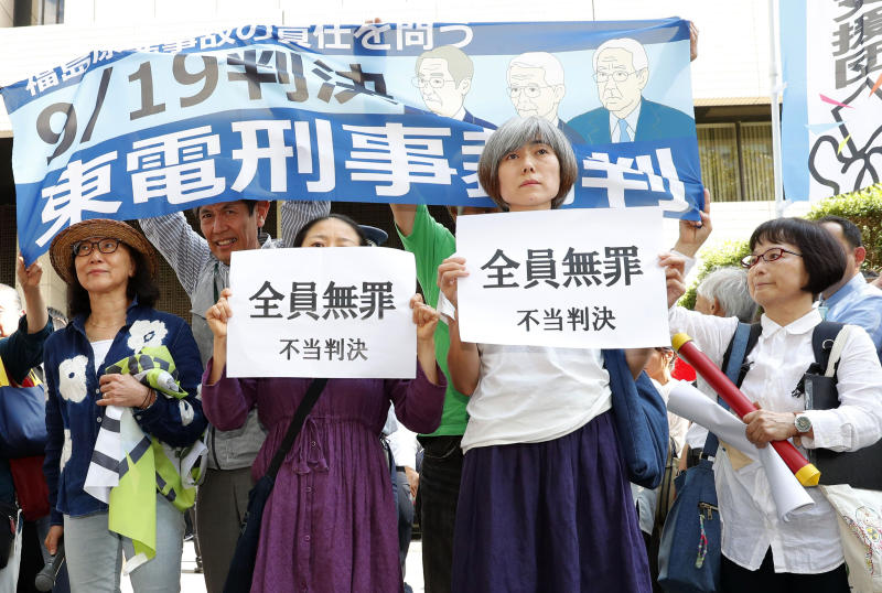 "A group of supporters of the trial shows banners reading ""unjust sentence"" in front of Tokyo District Court in Tokyo Thursday, Sept. 19, 2019. The court on Thursday ruled that three former executives for Tokyo Electric Power Company were not guilty of professional negligence in the 2011 Fukushima meltdown. It was the only criminal trial in the nuclear disaster that has kept tens of thousands of residents away from their homes because of lingering radiation contamination. (Satoru Yonemaru/Kyodo News via AP)"