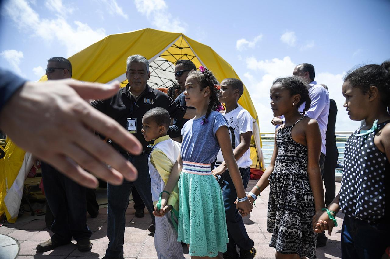 Children stand holding hands on Dock 6 after they were rescued from the cruise ship Caribbean Fantasy, in San Juan, Puerto Rico, Wednesday, Aug. 17, 2016. More than 500 passengers and crew were being evacuated on Wednesday from the burning ship about a mile off Puerto Rico's north coast. The mostly Dominican passengers included dozens of school-age athletes headed to competitions in Puerto Rico, including a 22-member cycling team, a girls' volleyball team and a boys' baseball team. (AP Photo/Carlos Giusti)