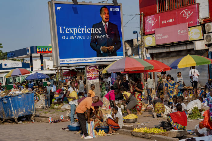 An election poster featuring President Denis Sassou N'Guesso stands over a market in central Brazzaville, Congo, Sunday March 7, 2021. Elections on Sunday March 21 will see President Denis Sassou N'Guesso poised to extend his tenure as one of Africa's longest serving leaders, 36 years, amid opposition complaints of interference with their campaigns. (AP Photo/Lebon Chansard Ziavoula)