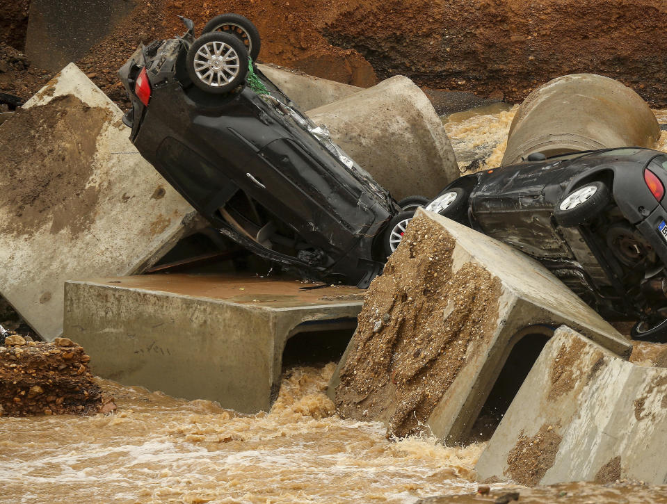 Cars lie in a washed out part of the Bessem district of Erftstadt, Germany, Friday, July 16, 2021. Heavy rains caused mudslides and flooding in the western part of Germany. Multiple have died and dozens are missing as severe flooding in Germany and Belgium turned streams and streets into raging, debris-filled torrents that swept away cars and toppled houses. (David Young/dpa via AP)