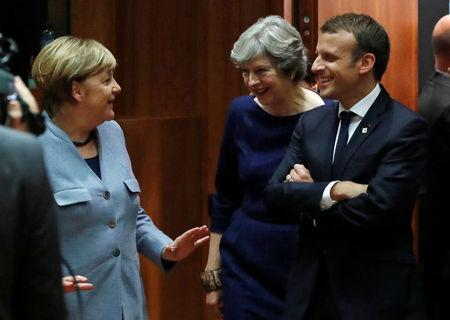 German Chancellor Angela Merkel (L) British Prime Minister Theresa May (C) and French President Emmanuel Macron arrive at a EU summit in Brussels, Belgium October 19, 2017. REUTERS/Yves Herman