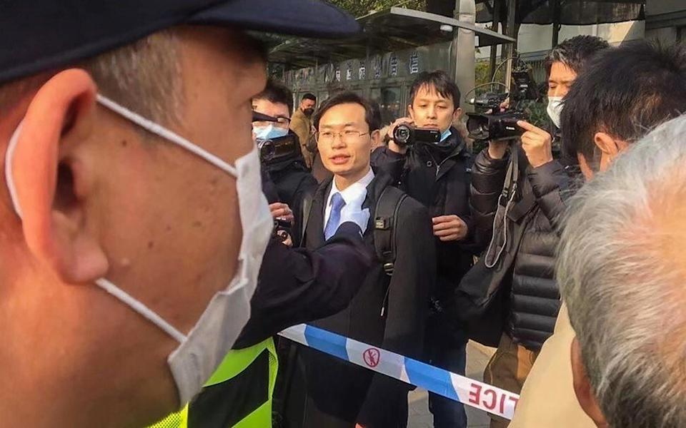 Zhang Zhan's lawyer Zhang Keke (centre) is stopped by police while talking to media shortly before Zhang Zhan's trial started on Monday. Photo: Handout