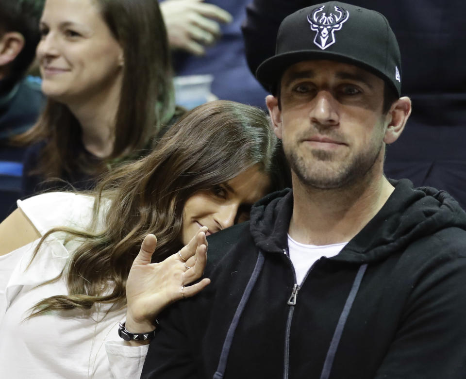"""FILE - In this April 20, 2018 file photo Danica Patrick and Green Bay Packers' Aaron Rodgers watch during the first half of Game 3 of an NBA basketball first-round playoff series between the Milwaukee Bucks and the Boston Celtics in Milwaukee. Patrick encountered some resistance from Rodgers when she wanted to set up a woman cave in the house they share in Green Bay, Wisconsin. The retired racecar driver proposed converting a bedroom into her own space. She says she got """"shut down"""" even though Rodgers has a man cave in the house. (AP Photo/Morry Gash, file)"""