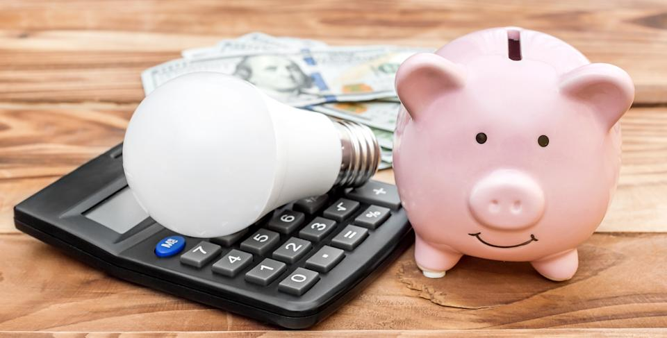 Piggy bank with light bulb, calculator and money on wooden background.