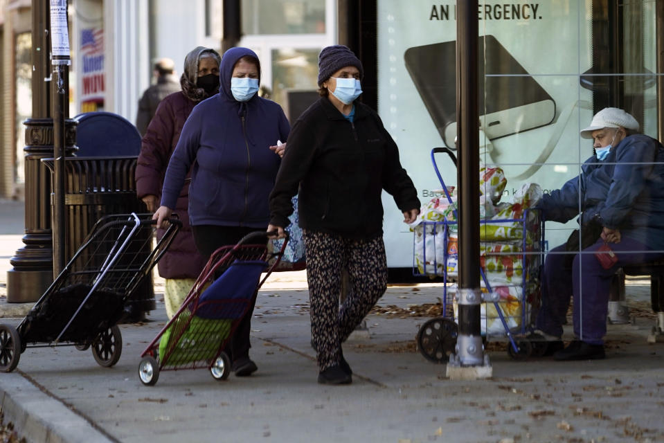 FILE - In this Nov. 12, 2020, file photo, people wear a face masks as they walk to an ICNA (Islamic Circle of North America) Relief Resource Center and Food Pantry during the COVID-19 pandemic in Chicago. In states like New Mexico and Washington and cities such as Philadelphia to Chicago, leaders are ordering or imploring residents to stay home to help stem a rising tide of infections that threatens to overwhelm the health care system. (AP Photo/Nam Y. Huh, File)