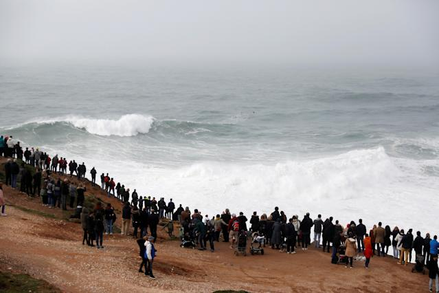 People gather to watch big waves at Praia do Norte in Nazare, Portugal, on Sunday. (Reuters)