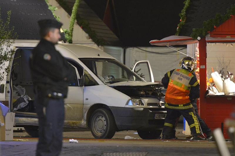 Firefighters inspect the van a driver used to plough into a Christmas market, injuring at least ten people before stabbing himself, in Nantes, France, on December 22, 2014 (AFP Photo/Georges Gobet)