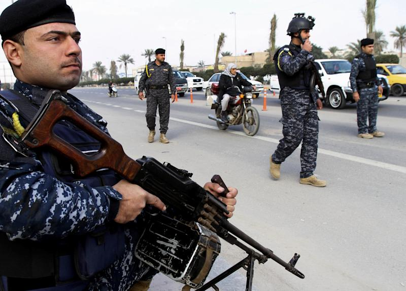 Iraqi federal policemen stand guard at a checkpoint in Basra, Iraq's second-largest city, 340 miles (550 kilometers) southeast of Baghdad, Iraq, Thursday, Jan. 2, 2014. The Iraqi government has tightened its security measures after security forces have arrested, Wathiq al-Batat, a controversial Shiite cleric who leads an Iranian-backed militia called Mukhtar Army. (AP Photo/Nabil al-Jurani)