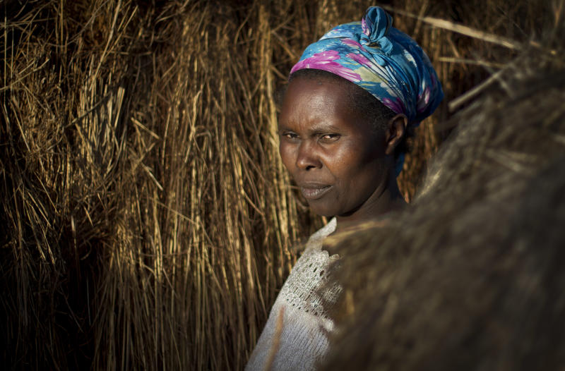 In this Saturday Feb. 9, 2013 photo, Damaris Wanjiku Mathu, 35,, stands outside her straw hut at 'Hope' camp for internally-displaced Kenyans from the Kikuyu tribe, near Nyahururu, in Kenya. The 624 people living at Hope Camp, a spot near the equator in a placed called Laikipia, is an illustration of one of the many lingering effects of the tribe-on-tribe violence that rocked Kenya after its 2007 presidential election. Five years later _ and now only days before the country's March 4 presidential election _ hundreds of refugees still have not returned home. (AP Photo/Ben Curtis)