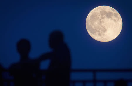 People stand and look at the moon one day ahead of the Supermoon phenomenon from a bridge over 42nd St. in the Manhattan borough of New York