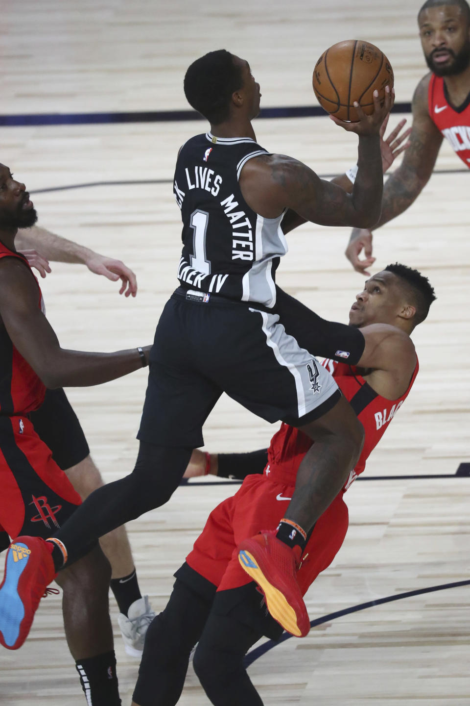 San Antonio Spurs guard Lonnie Walker IV (1) runs into Houston Rockets guard Russell Westbrook (0) while attempting a shot, resulting in an offensive foul during the second half of a NBA basketball game Tuesday, Aug. 11, 2020, in Lake Buena Vista, Fla. (Kim Klement/Pool Photo via AP)