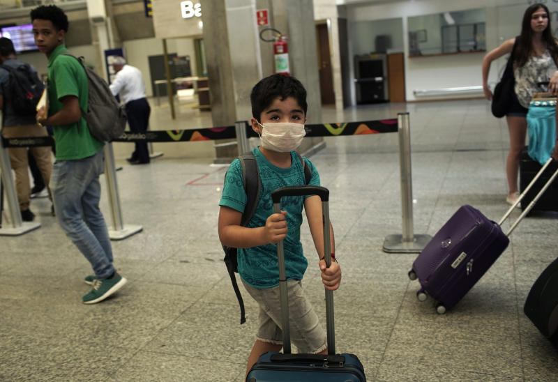 A child wearing a mask arrives to the Antonio Carlos Jobim Galeao International Airport, in Rio de Janeiro, Brazil, Friday, Jan. 31, 2020. Passengers and airport workers are voluntarily wearing masks as a precautionary measure amid an outbreak of the coronavirus that started in China. (AP Photo/Silvia Izquierdo)