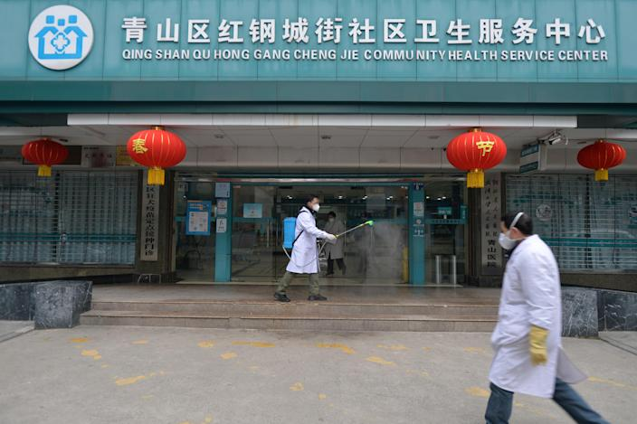 A doctor disinfects the entrance of a community health service center, which has an isolated section to receive patients with mild symptoms caused by the novel coronavirus and suspected patients of the virus, in Qingshan district of Wuhan, Hubei province, China February 2, 2020. Picture taken February 2, 2020. China Daily via REUTERS