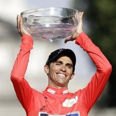 Saxo Bank Team cyclist Alberto Contador celebrates at the podium as he holds Spanish vuelta cycling race trophy after riding the final stage along 115 km (71 miles) from Cerdedilla to Madrid, on Sunday, Sept. 9, 2012. This is the second time Contador wins the Spanish vuelta, who also has a pair of Tour de France and one Giro d'Italia. (AP Photo/Alberto Di Lolli)