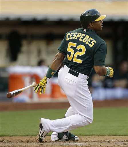 Oakland Athletics' Yoenis Cespedes drops his bat after hitting an RBI single off Cincinnati Reds' Bronson Arroyo in the third inning of a baseball game Tuesday, June 25, 2013, in Oakland, Calif. (AP Photo/Ben Margot)