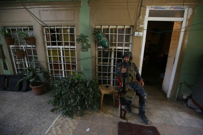 A member of the Iraqi security forces sits in the courtyard of a house on the front line in Mosul's Old City on May 3, 2017