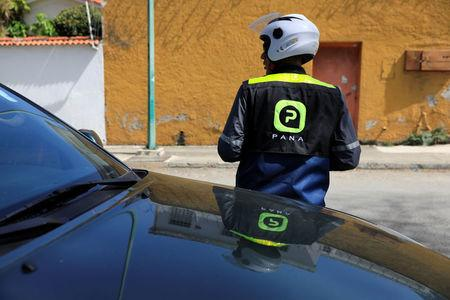 An employee of Pana, a mobile application which dispatches security crews to stranded drivers who request help, stands guard as he assists a client in Caracas, Venezuela June 15, 2018. Picture taken June 15, 2018. REUTERS/Adriana Loureiro