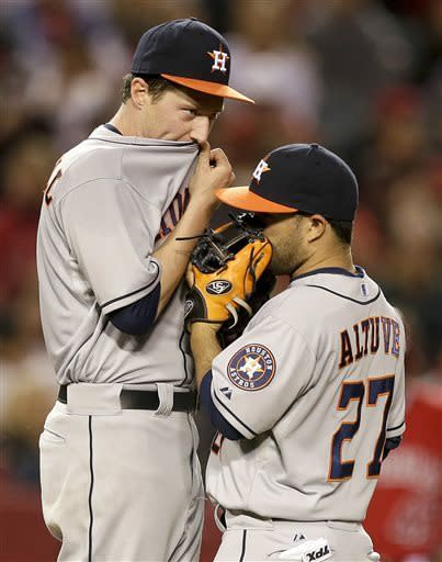 Houston Astros starting pitcher Lucas Harrell, left, and second baseman Jose Altuve talk on the mound during the fifth inning of a baseball game against the Los Angeles Angels in Anaheim, Calif., Saturday, April 13, 2013. (AP Photo/Chris Carlson)