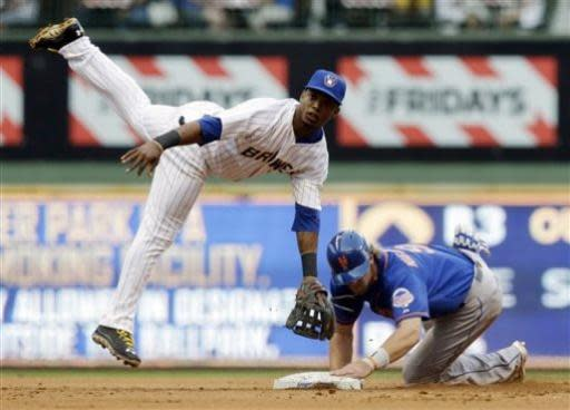 New York Mets' Kirk Nieuwenhuis breaks up a double play as Milwaukee Brewers shortstop Jean Segura throws to first on a ball hit by Juan Lagares tduring the first inning of a baseball game Friday, July 5, 2013, in Milwaukee. (AP Photo/Morry Gash)