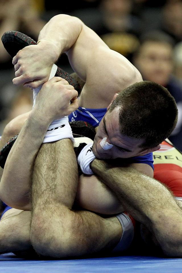 IOWA CITY, IA - APRIL 22: Josh Churella (red) wrestles Brent Metcalf (blue) in the 66 kg freestyle weight class during the challenge tournament for the finals of the US Wrestling Olympic Trials at Carver Hawkeye Arena on April 22, 2012 in Iowa City, Iowa. (Photo by Matthew Stockman/Getty Images)
