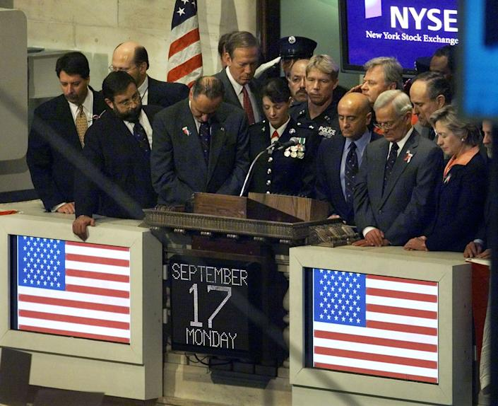 Dignataries bow their heads during a moment of silence in honor of the victims of the World Trade Tower disaster, on the floor of the New York Stock Exchange in New York September 17, 2001. This is the first day of trading since two hijacked jetliners crashed into the twin towers of the World Trade Center on September 11. REUTERS/Jeff Christensen  JC/SV