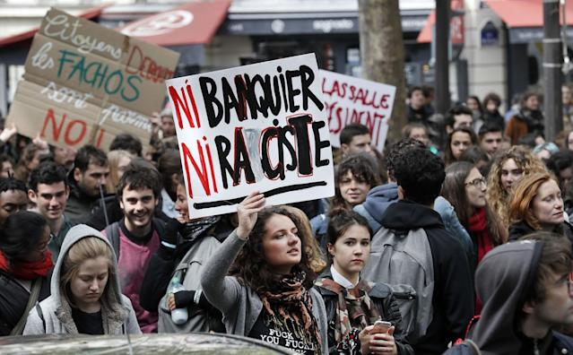 """<p>Students hold a placard reading """"Neither banker, nor racist"""" during a demonstration in Paris on April 27, 2017 to protest against the results of the first round of the French presidential election. (Thomas Samson/AFP/Getty Images) </p>"""