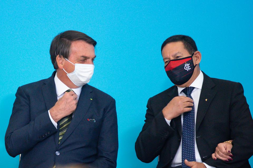 BRASILIA, BRAZIL - AUGUST 28: (L-R) President of Brazil Jair Bolsonaro and Vice President of Brazil Hamilton Mourão talk during celebration of National Volunteer Day amidst the coronavirus (COVID-19) pandemic at the Planalto Palace on August 28, 2020 in Brasilia. Brazil has over 3.761,000 confirmed positive cases of Coronavirus and has over 118,649 deaths. (Photo by Andressa Anholete/Getty Images)