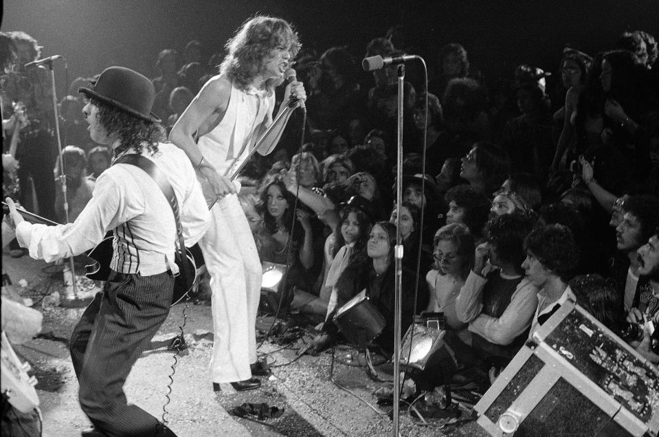 "Rock group ""The New York Dolls"" perform at the Waldorf Halloween Ball, Waldorf-Astoria Hotel, NYC, Oct. 31, 1973. At right is lead singer David Johansen, with guitarist Sylvain Sylvain. (AP Photo/Richard Drew)"
