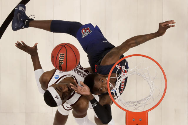 Liberty guard Lovell Cabbil Jr., right, shoots over Mississippi State forward Aric Holman during the second half of a first-round game in the NCAA mens college basketball tournament Friday, March 22, 2019, in San Jose, Calif. (AP Photo/Ben Margot)