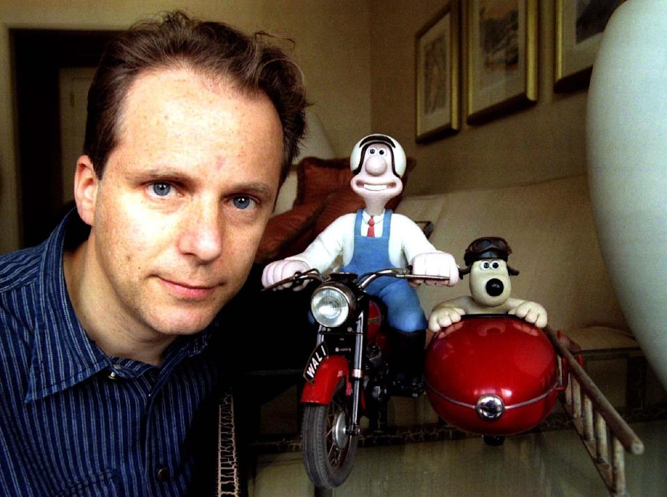 """Nick Park of Britain poses with his creations, plasticine figures Wallace (C) and Gromit, (R) in a New York hotel October 21. Wallace and Gromit, who appeared in the 1996 Oscar winning animated short film """"A Close Shave"""", were returned to Park after being left in a taxi October 19."""