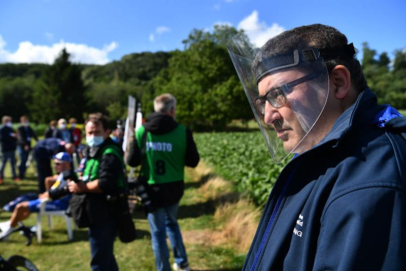 One man wears a face shield to watch the race