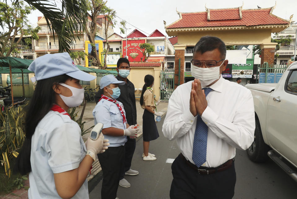 Cambodian Education Minister Hang Chuon Naron, right, greets students during his visit to Santhormok high school, in Phnom Penh, Cambodia, Monday, Nov. 2, 2020. Schools throughout Cambodia that had been shut in March because of the coronavirus crisis reopened Monday, but with limits on class sizes and hours.(AP Photo/Heng Sinith)