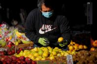 A man wears a mask and gloves as he shops at a fruit stand, during the outbreak of the coronavirus disease (COVID-19), in Brooklyn, New York